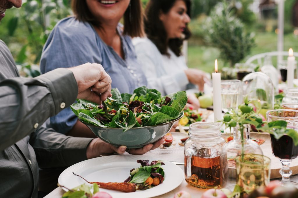 Family having dinner and salad outdoors